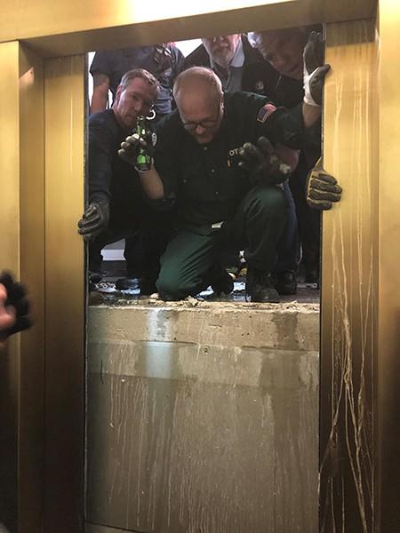 Lực lượng cứu hộ phá tường mở cửa thang máy. Ảnh: ABC 7 Chicago